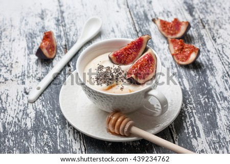 yogurt with pieces of fig, chia seeds, honey in a white cup on a wooden background - stock photo