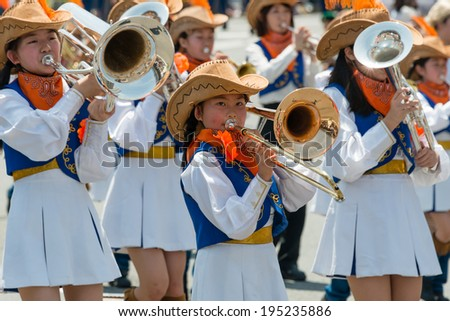 """YOKOHAMA, JAPAN - MAY 3, 2014: Children are marching on the street in """"The Yokohama Parade"""". The parade marks the beginning of the """"Opening of the Port Festival"""" which is held every year since 1953. - stock photo"""