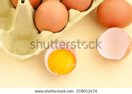 Yolk in an eggshell. Eggs in the package on a wooden background. - stock photo