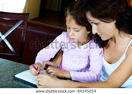 Yong brunette mother in her thirties helping her daughter with drawing homework while sitting at home. - stock photo