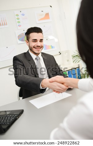 yong businessman in transaction shaking hand with client  - stock photo