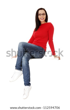 Yong casual woman sitting on something - stock photo