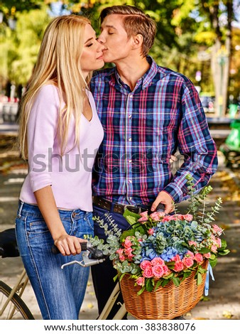 Yong couple with retro bike kissing in park. - stock photo