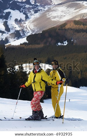 Yong family skiers in yellow on ski slope - stock photo