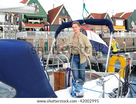 yong man steering yacht from berth - stock photo