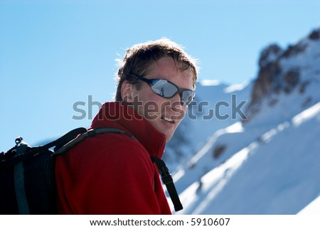 Yong man travels in winter mountain - stock photo