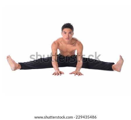 yong muscular man sitting and making stretching exercises - stock photo