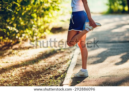 yong sporty woman streching her leg in the summer park - stock photo