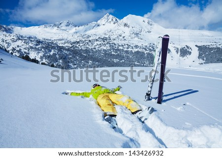 Yong woman laying in snow with her ski standing close with mountain on the background - stock photo