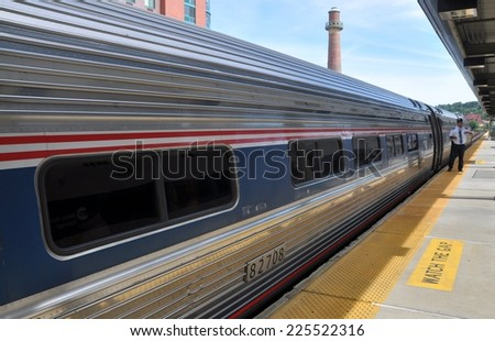 Yonkers, NY - August 6, 2012:  Conductor on the platform of the Yonkers Railway station standing next to an AMTRAK passenger train enroute to NYC - stock photo