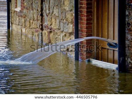 York floods. Water being pumped out of letterbox in door.