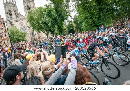 YORK, UNITED KINGDOM - JULY 6, 2014: People watch the Tour de France peleton riding past York Minster in York, UK. Tour De France is one of the most prestigious cycling contests in the world.  - stock photo