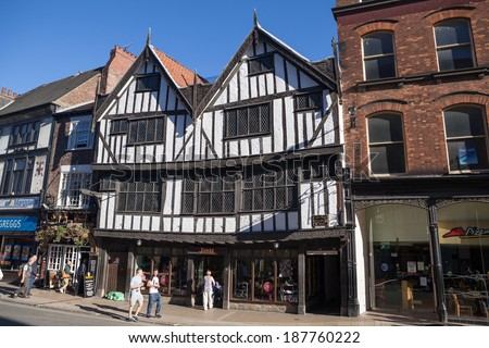 YORK, UNITED KINGDOM - SEPTEMBER 22, 2013: York's oldest Tudor building, the 16th century house called Sir Thomas Herbert's House, classified as Grade I English Heritage Building. Pedestrians pass by. - stock photo