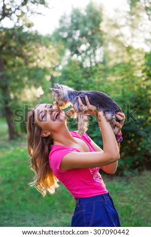 Yorkshire terrier licks his owner. portrait of young smiling woman with her small dog outdoor in summer sunny day - stock photo