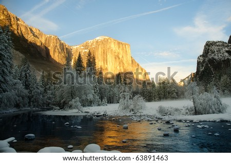 Yosemite valley at sunset with golden rays of sunlight on El Capitan and beautiful reflection from the Merced river in winter - stock photo