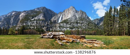 Yosemite Valley panorama showing the upper and lower Yosemite Falls with a decaying tree in the foreground - stock photo
