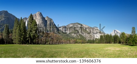 Yosemite Valley panorama showing the upper Yosemite Falls, the Half Dome with Yosemite meadow in the foreground - stock photo