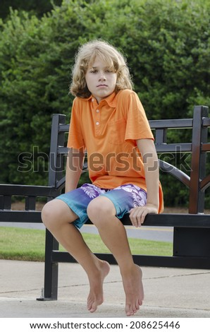 You boy sits patiently on a bench for his friend - stock photo