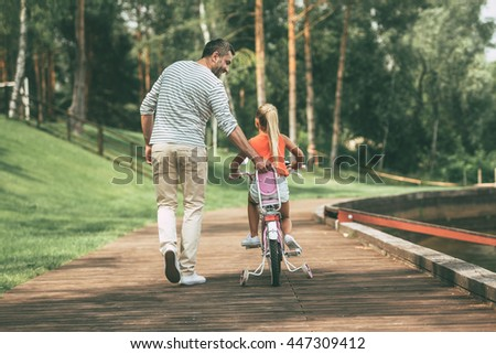 You can do it! Full length rear view of cheerful father teaching his daughter to ride a bicycle in park