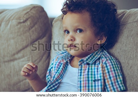 You can drown in his eyes. Portrait of little African baby boy looking away while sitting on the couch at home