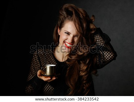You can't go wrong with cup of barista made good Italian coffee. Portrait of cheerful woman with long wavy brown hair and red lips holding cup of coffee on dark background