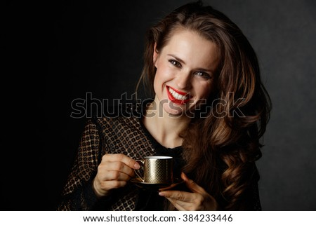 You can't go wrong with cup of barista made good Italian coffee. Portrait of smiling woman with long wavy brown hair and red lips holding cup of coffee against dark background