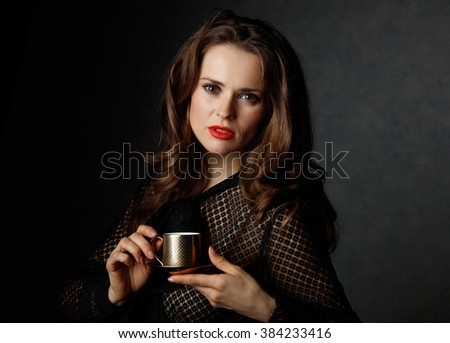 You can't go wrong with cup of barista made good Italian coffee. Portrait of woman with long wavy brown hair and red lips holding cup of coffee against dark background