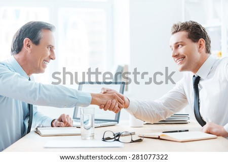 You deserve your success. Side view of two business people shaking hands while sitting at the table in office - stock photo