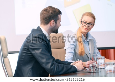You did a great job. Business manager in a black suit and his attractive female colleague smiling at each other - stock photo