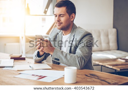 You have new message! Handsome young man using his smartphone with smile while sitting at his working place - stock photo
