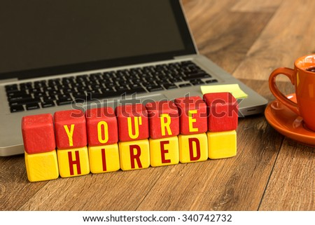 You're Hired written on a wooden cube in a office desk - stock photo