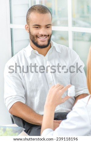 You will be healthy. Confident doctor giving the drugs to a patient while sitting at a desk in the office