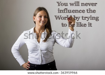 You will never influence the World by trying to be like it - Beautiful girl writing on transparent surface - horizontal image - stock photo