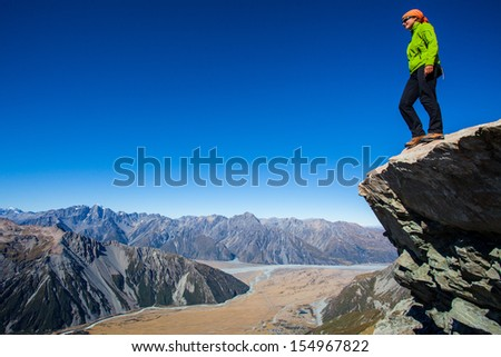 Youg woman high above the alpine valley - stock photo