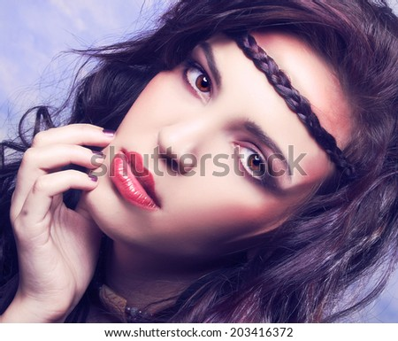 Youg woman with long dark hair posing in hippie image