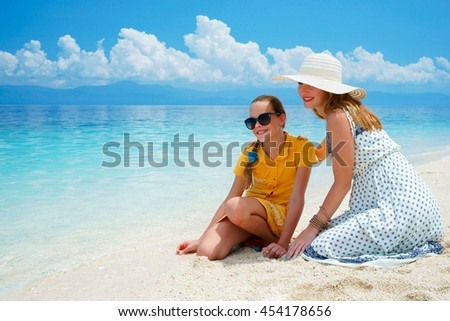 Youn europian woman in light dress is sitting on the white sand beach near beautiful tropical sea and cares about her teen daughter at sunny day - stock photo