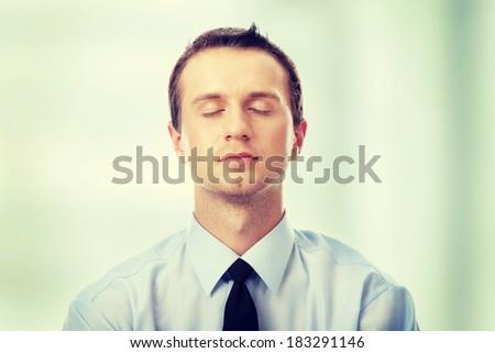 Yound caucasian business man meditating - stock photo