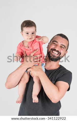 Yound daddy rising his son up while smiling - stock photo