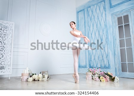 Young a beautiful ballerina is dancing in the studio - stock photo