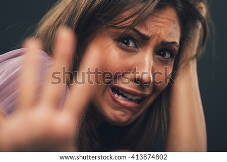 Young abused woman defending with pray looking at camera with outstretched arm. Selective focus. Focus on background, on woman face. - stock photo