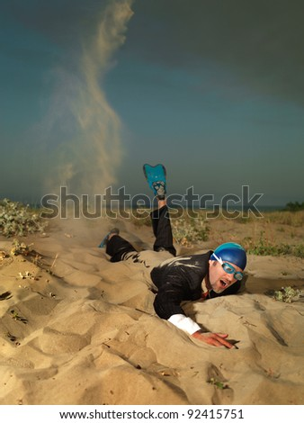 young, active businessman, dressed in a black suit, swimming through the sand on the sea shore; conceptual