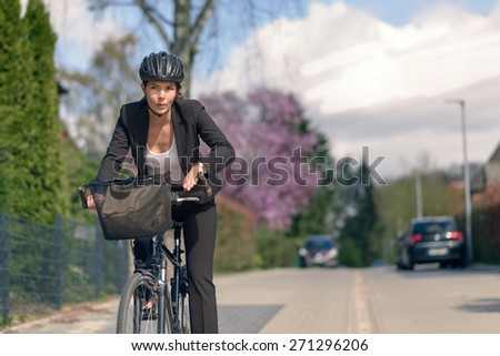 Young Active Businesswoman Commuting on a Bicycle with Protective Helmet Going to her Office - stock photo