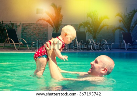 Young active father playing with a cute baby - stock photo