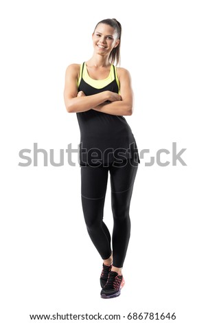 Young active healthy fit woman in sportswear smiling at camera with crossed hands. Full body length portrait isolated on white background.