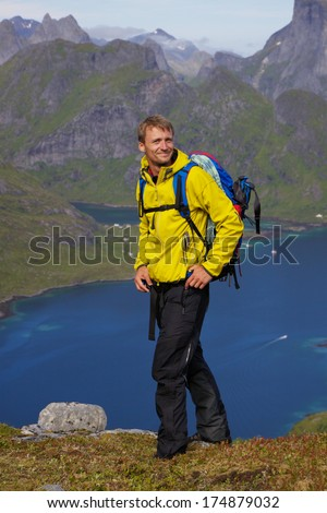 Young active man with backpack hiking on Lofoten islands in Norway on sunny day - stock photo