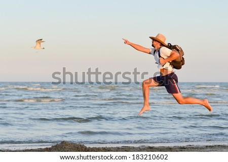 Young active man with backpack jumping high and running at seashore on the outdoors summer background