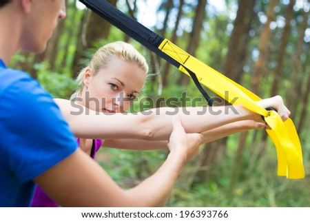 Young active people does suspension training with fitness straps outdoors in the nature. - stock photo
