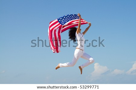 young active woman holding american flag and jumping on beach - stock photo