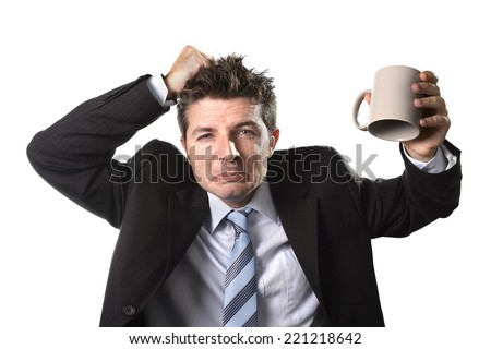 young addict business man in suit and tie holding empty cup of coffee anxious , desperate and crazy in caffeine addiction and need to keep awaken isolated on white background - stock photo