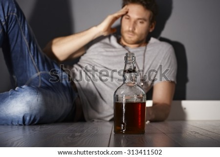 Young addicted man with a bottle of whiskey. - stock photo